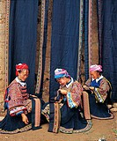 Su Miao women embroidering in front of batik clothing, Dabatun, Machang Village, Shechang, Longlin, Baise, Guangxi Province, China