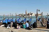 Young people sitting at the Piazza San Marco, watching as the gondolas rocking Grand Canal in Venice, Italy