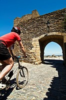 A mountain biker rides through the streets of the historic village of Monsaraz, Alentejo, Portugal