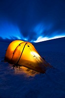 A tent iluminated at night on snow