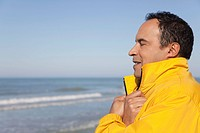 Mature man at the beach on a chilly day, eyes closed, portrait