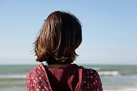 Woman contemplating the ocean, rear view