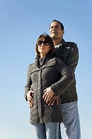 Couple standing together outdoors, man embracing woman from behind