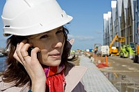 Female architect using cell phone at construction site, portrait
