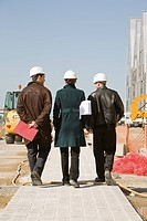 Property developers walking at construction site, rear view