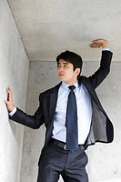 Businessman standing in corner putting his hands on wall