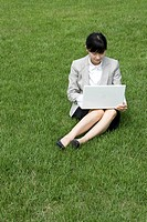 Busenesswoman using a laptop on grass