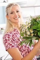 blond woman holding a bunch of wild herbs