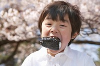 Boy with rice ball in his mouth, Tokyo Prefecture, Honshu, Japan