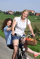 two young woman on one bike