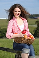 young brunette woman holding basket with apples