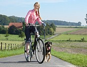 woman biking, dog running beside