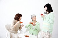 Three generations of women drinking tea
