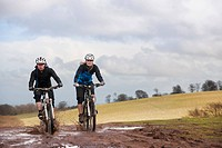Couple riding bike through muddy puddles