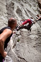 Rock climber securing partner