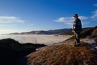 A man looks down upon a remote and rugged coastline from a hilltop.