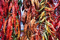 Dried chillies hanging in market.
