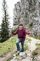 Man with hiking poles on mountain trail