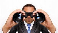 Business Man in a Suit Looking Through Binoculars
