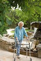 Elderly woman with a walker walking outside.