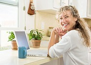 Mid_age woman using laptop at home
