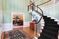 Foyer in luxury home with carpeted staircase