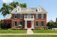 Brick home with columned entry and front balcony