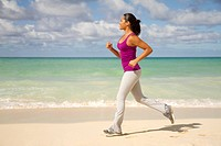fit hispanic girl jogging on beach