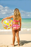 Girl with beach ball looking out at ocean.