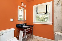 Powder room in suburban home with orange walls