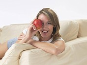 Woman on the sofa with an apple