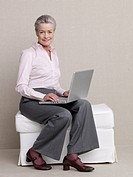 Senior citizen in business wear using a laptop