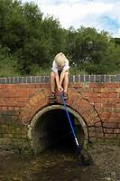 Boy fishing with net from bridge