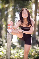 Asian woman smiling and stretching.