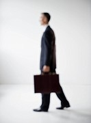 Businessman with briefcase walking, defocused