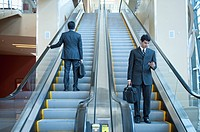 Businessmen standing on escalators