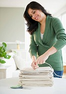 Smiling Hispanic woman trying newspapers in bundle