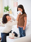 Mother wiping sick daughter´s nose with tissue
