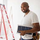 African American construction worker carrying solar panel (thumbnail)