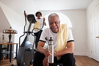 Black woman using elliptical machine, husband drinking water