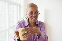 Smiling Black woman drinking coffee
