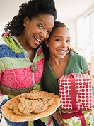 Mother and daughter carrying birthday gift and cookies