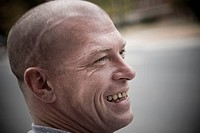 Mid adult man with shaved head smiling