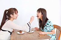 Young women eating cake