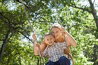 Mother pushing little boy on a swing
