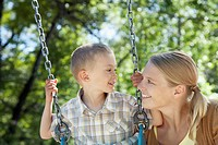 Mother pushing son on a swing