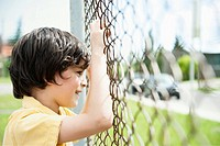 Boy standing by fence