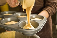 Cook pouring batter into muffin tin