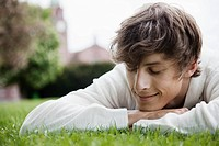 Young man lying in grass (thumbnail)