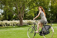 Young woman riding bicycle in grass (thumbnail)